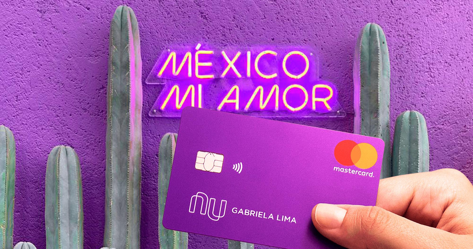 """Cactos em fundo roxo, com as escritas em neon na parede """"México Mi Amor"""". Em primeiro plano, uma mão segura o cartão roxo do Nubank"""