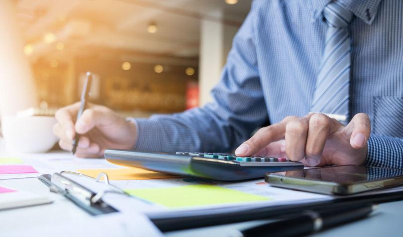 Homem fazendo cálculos calculadora mesa com papeis