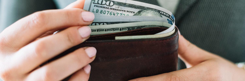 Close up de uma carteira segurada por duas mãos, retirando notas de dólares dela